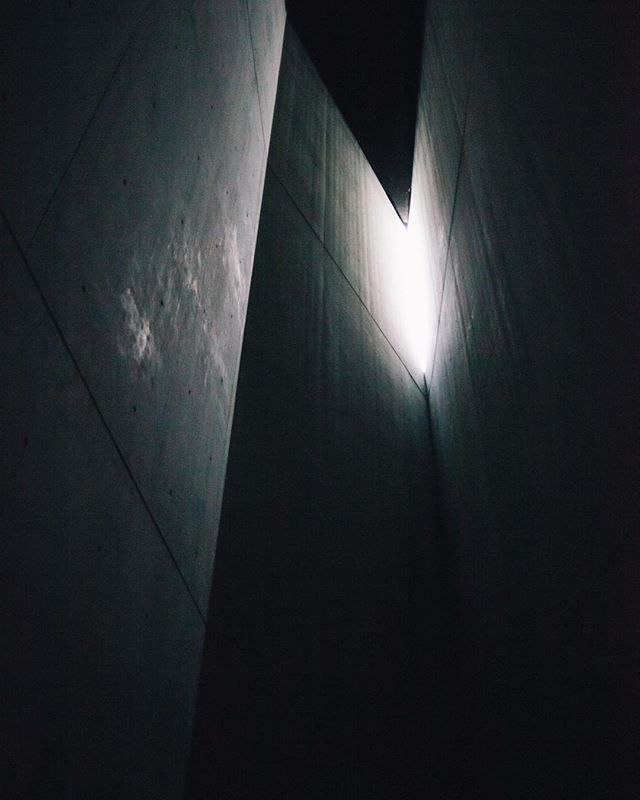 A tiny slit towards the ceiling of 'The Holocaust Tower' inside Daniel Libeskind's Jewish Museum allows a small fragment of light to penetrate a void of darkness, with sounds of the outside world eerily permeating the space. Standing shrouded beneath immense concrete walls gives a macabre feeling of isolation and panic; symbolic of what Jewish deportees experienced on Nazi Holocaust trains.