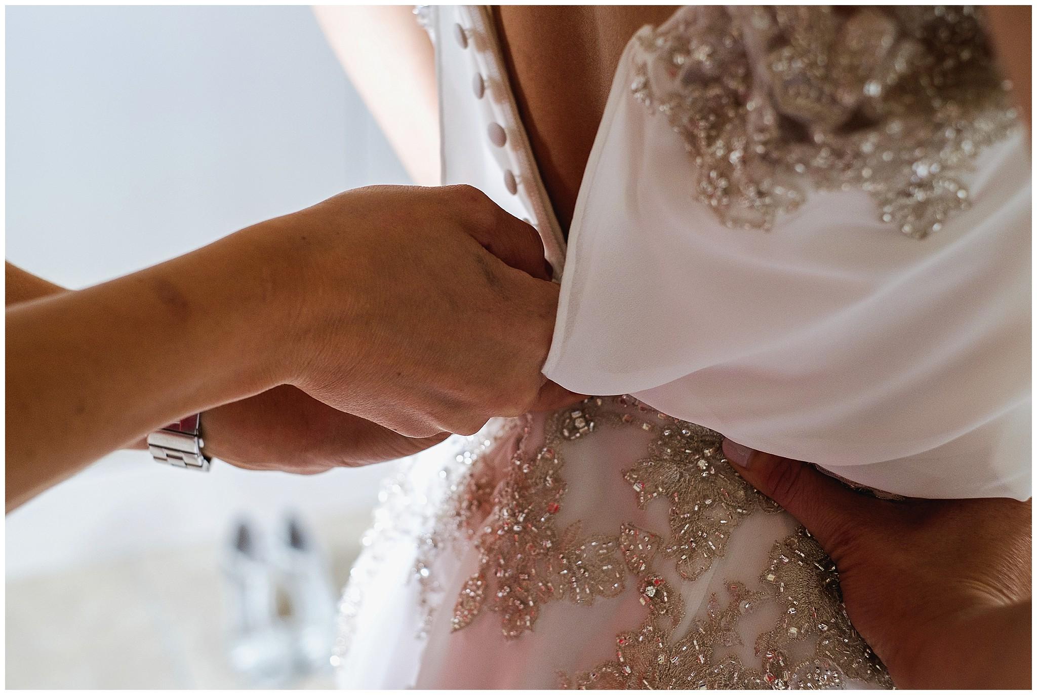 brides dress being fastened