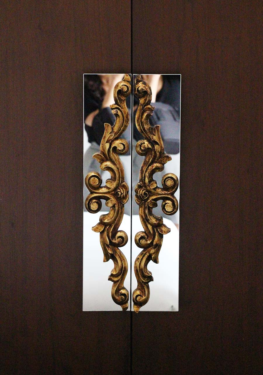 Gold leaf wooden handles on a chic closet door -  Hotel B .