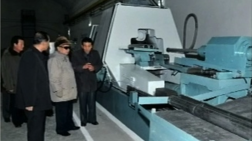 An example of the open-source evidence used for Kemp's study:A 2011 image from a television broadcast in North Korea showing Kim-Jong Il inspecting a flow-forming machine located in an underground tunnel. This type of machine is able to produce centrifuge rotors for North Korea's uranium-enrichment program.