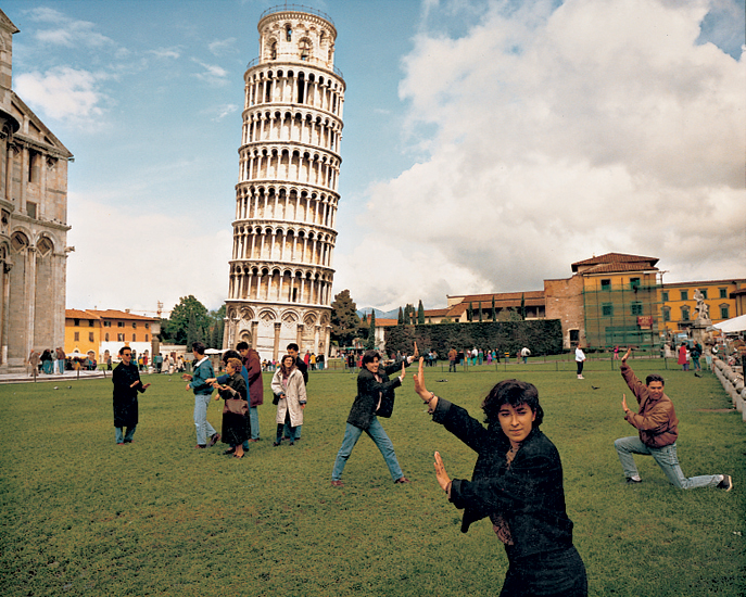© Martin Parr 1990 Small World: The Leaning Tower of Pisa, Italy (Permission granted). Tourists pose as if holding the famous tower.