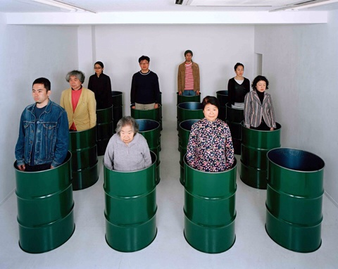 Oil Can, bt Tatsumi Orimoto. In a small white room, expressionless Asian people stand in green 44 gallon oil drums.