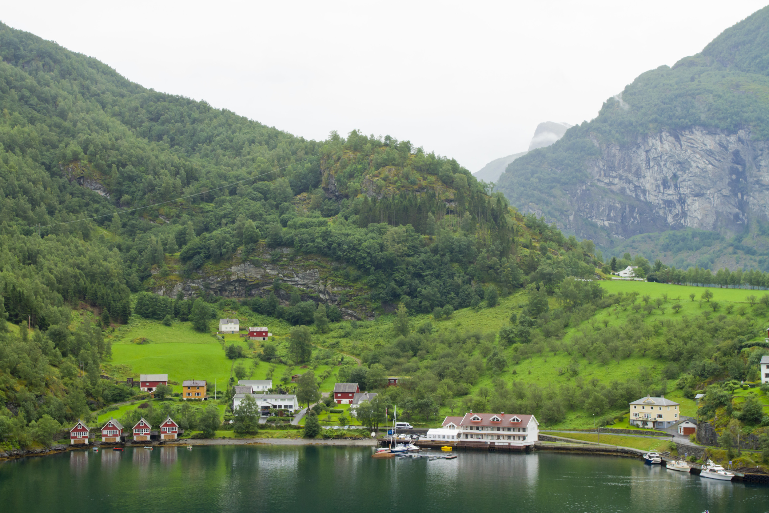 1. Small wooden cabins line the shore of the Aurlandsfjorden, dominated by the steep forested mountains in the background. The water is still, with very little activity.