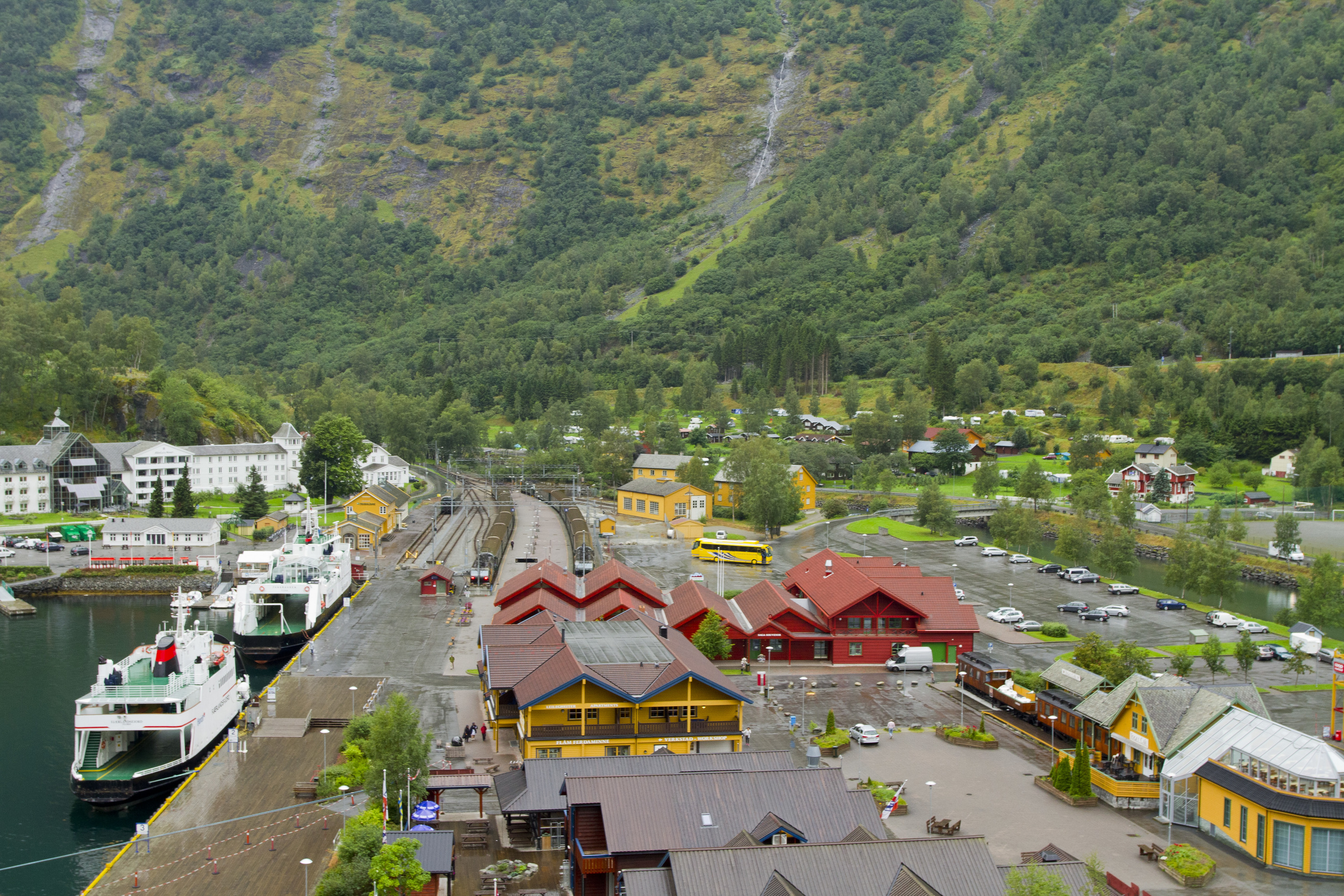 2. Flam is derived from the Old Norse word flá, which means a plain between steep mountains. The image above shows the flat land of theflood plains of the Flåm River. Empty ferries are docked, the car parks are quiet around the retail outlets towards the centre of the image. In the background waterfalls can be seen flowing towards the left of the frame.