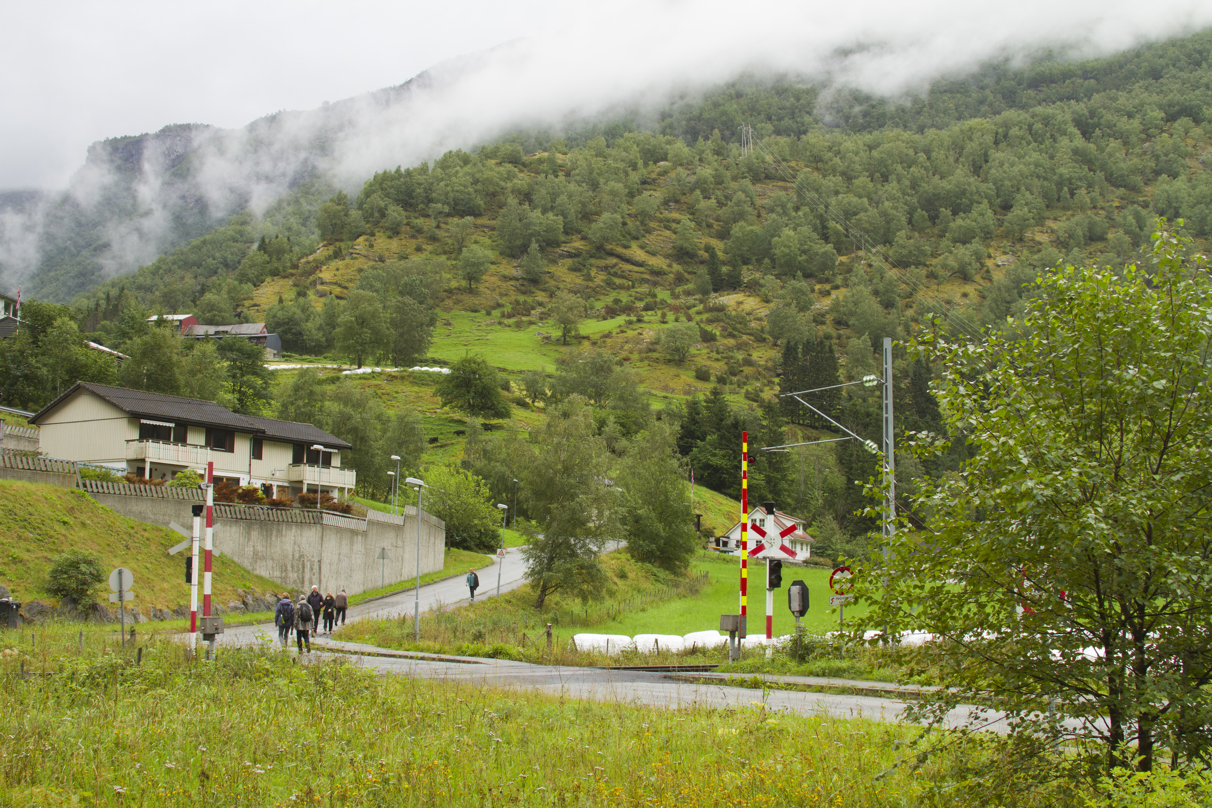 4. Walkers can be seen following the winding road up towards the steep mountain slope with the railway safety barriers opened up. Again the characteristic mist covers the trees in the upper-most part of the image.