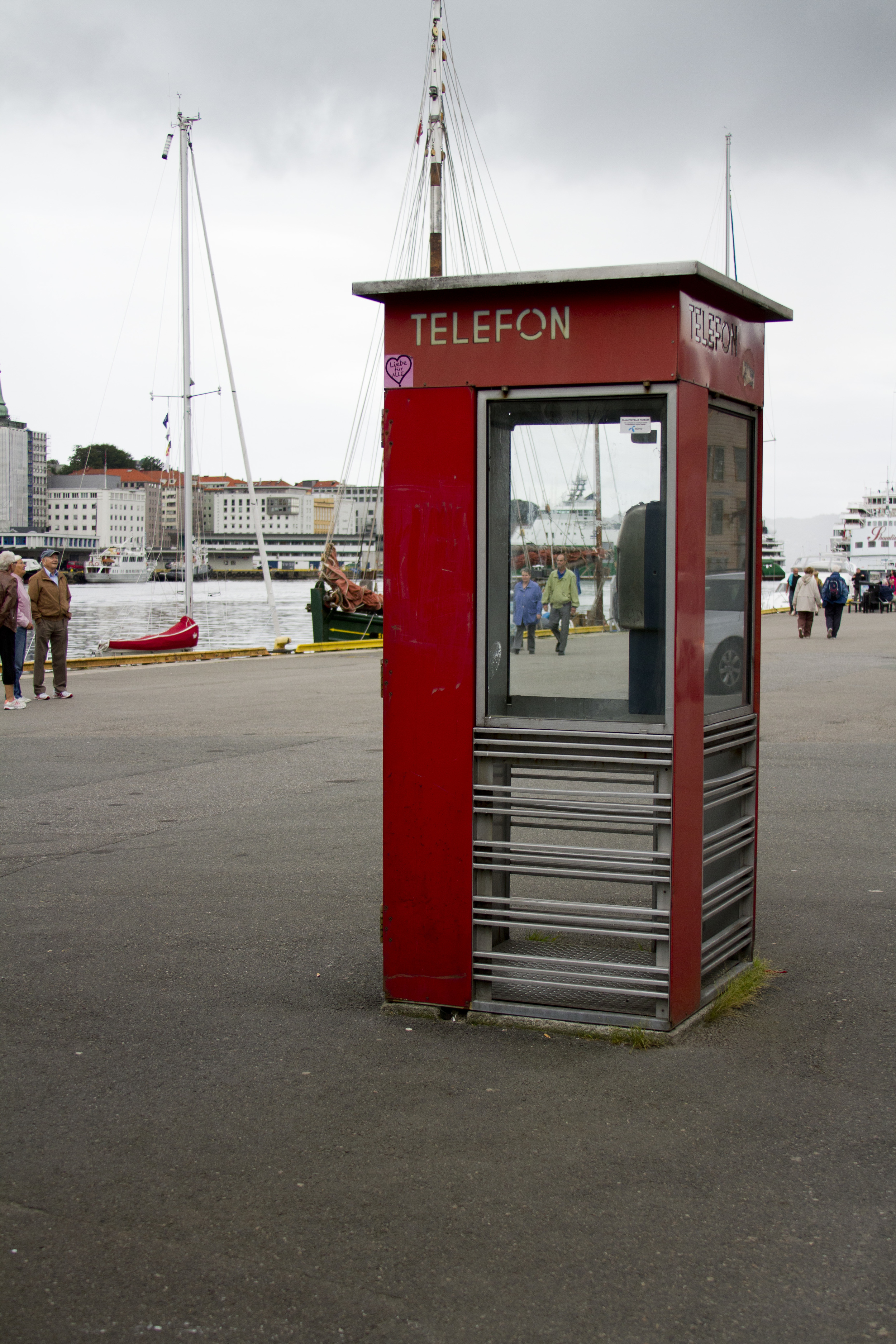 f/3.5  ISO 400  30mm  1/750   5. In today's hi-tech world of smart phones, it was a novelty to find a phone box. It was unused , so I waited until I could capture two people in the window, albeit outside opposite. For me it signifies the remoteness of Bergen.
