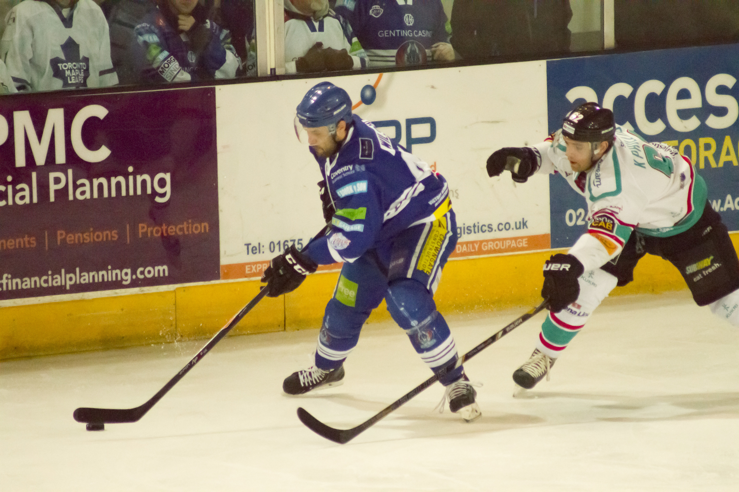 The key feature of a sports image is often when a player is shown to be in possession. The moment in this image is the Coventry Blaze (blue) player's hockey stick in contact with the puck.