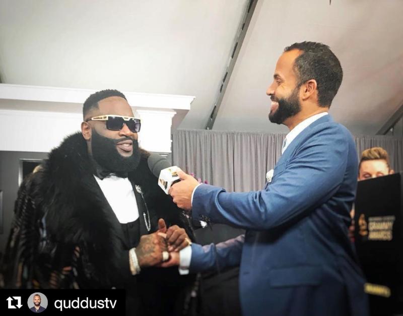 Quddus interviews Rick Ross at the 60th Grammy Awards wearing Fleur'd Pins lapel flower.jpg