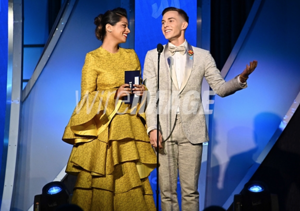 Lilly Singh and Adam Rippon, wearing Fleur'd Pins PRIDE Satin Dahlia,  speak onstage during the 30th Annual GLAAD Media Awards photo by Astrid Stawiarz.png