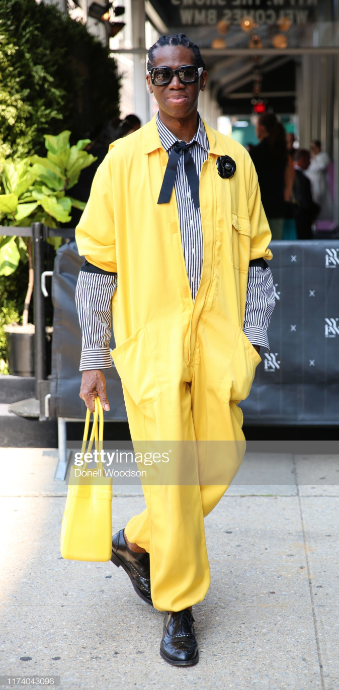 Miss J Alexander is seen wearing Fleur'd Pins Large Black Patent Leather Camellia with a yellow jump suit with matching yellow bag and black shoes during New York Fashion Week on September 11, 2019 in New York City.png