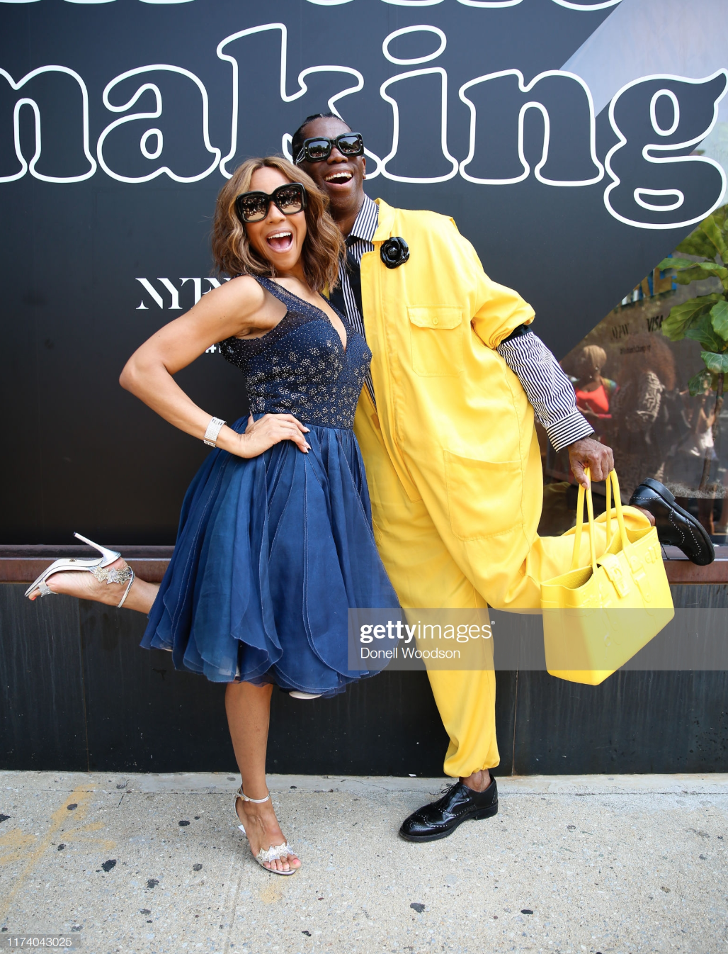 Deborah Cox and Miss J Alexander seen wearing Fleur'd Pins Large Black Patent Leather Camellia with a yellow jump suit with matching yellow bag and black shoes during New York Fashion Week on September 11, 2019 in New York City.png