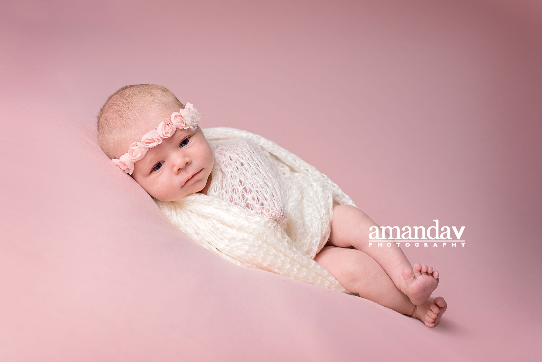 baby wrapped in white wrap with rosette tieback