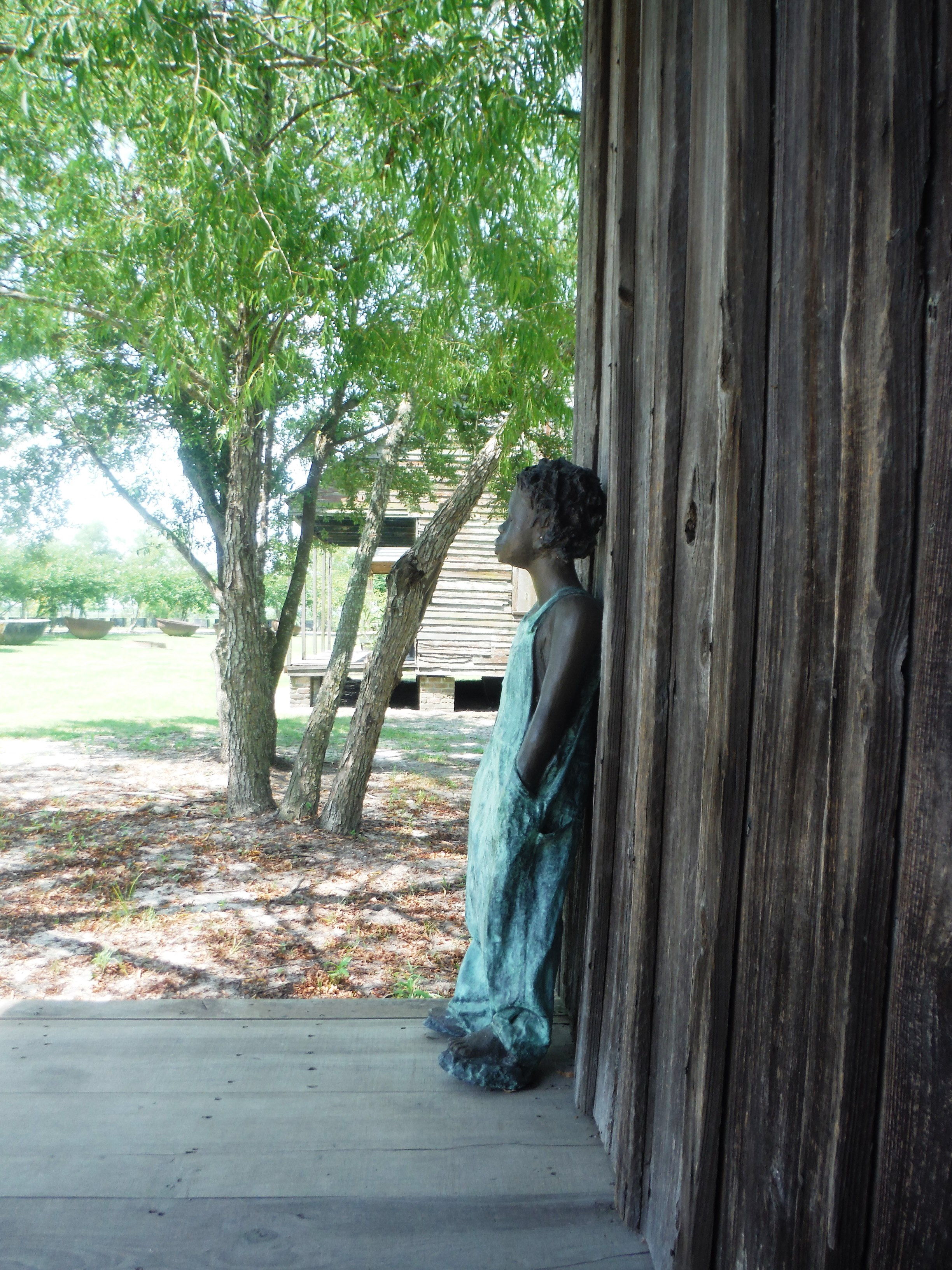 A bronze statute depicts cabin life as it might have been for a young slave in the mid-19th century.