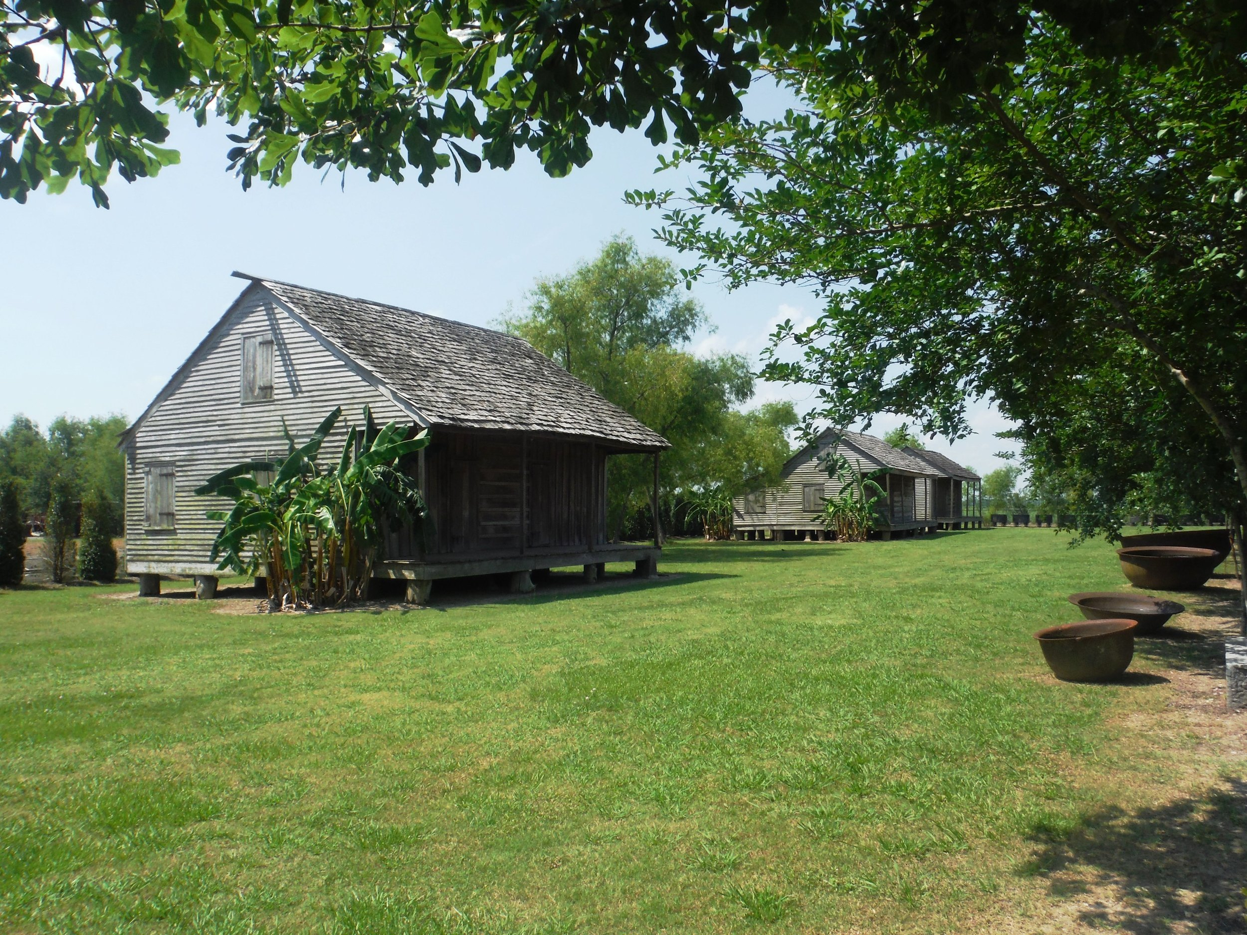 Slave cabins at the Whitney Plantation were preserved and grouped on the site from neighboring plantations. Old sugar processing bowls lie in the hot sun to the right of the cabins.