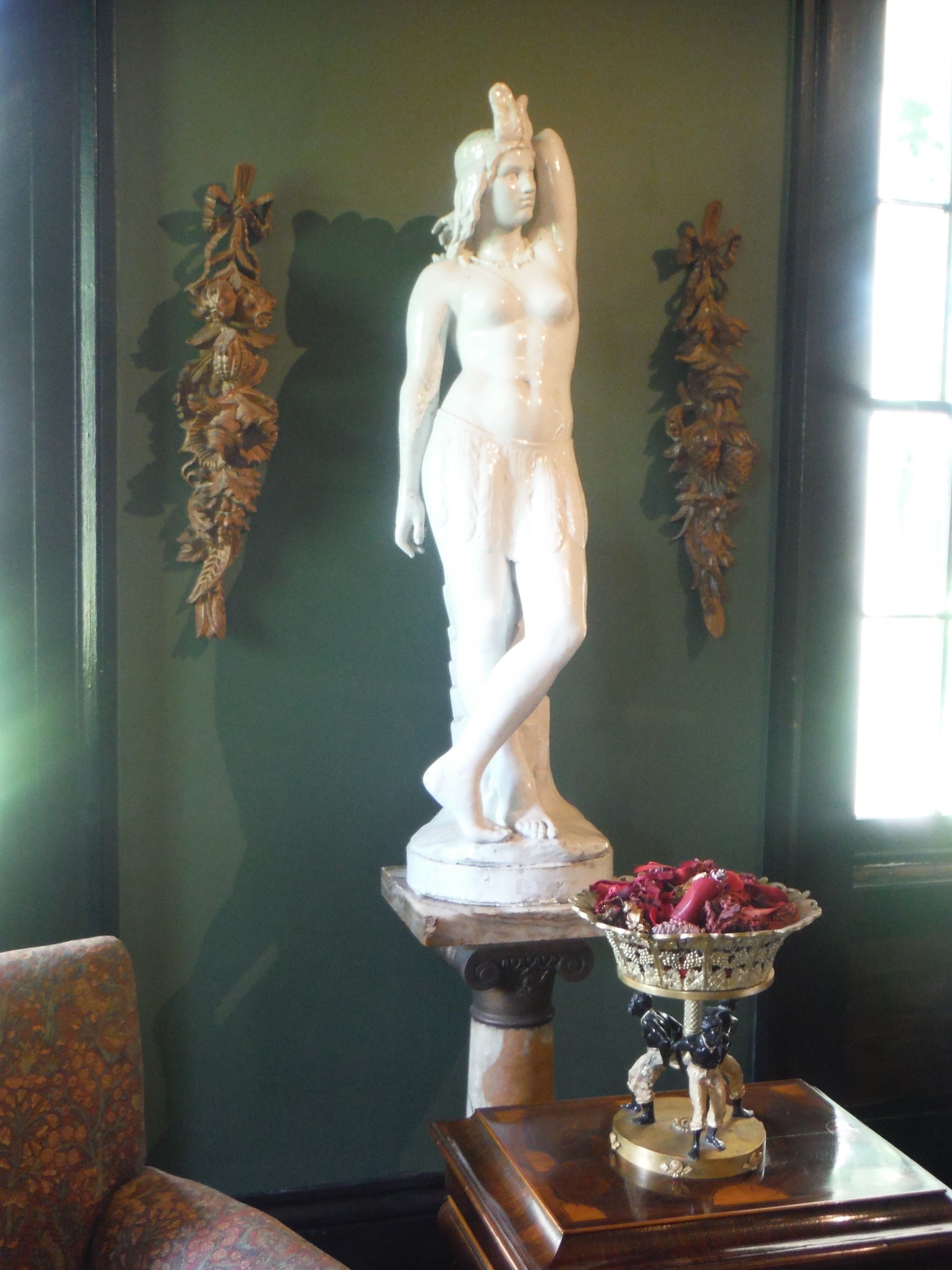 High art in the men's sitting room at Houmas House included this marble statue of a Native American. Below it, slaves are depicted lifting the ornate bowl of a golden candy dish.