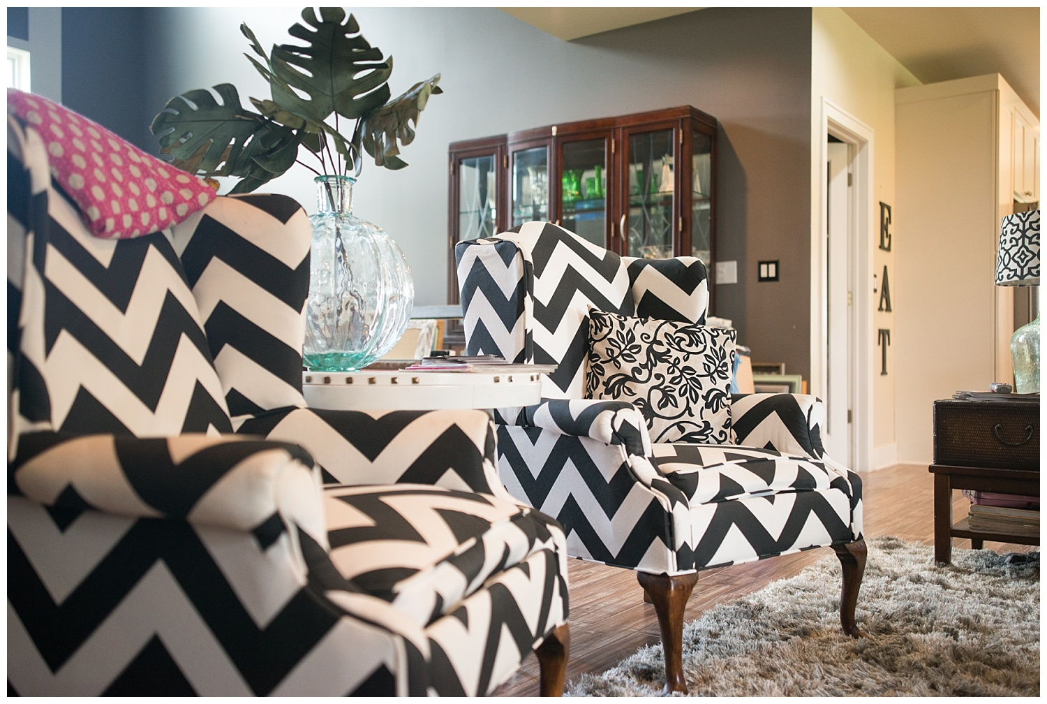 "Just beyond these bold reupholstered chairs is her dining room which is completely taken over with goods ready to go to Covered Bridge.  To the right of where you see the ""EAT"" letters is her kitchen.  And check out that cozy shag rug to soften up the living room area."