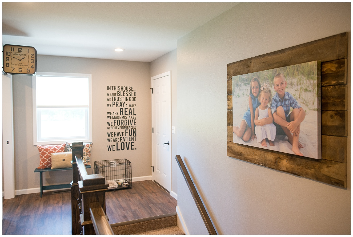 The double-sided clock from Fresh Digs hangs at the end of the lockers and leads into the laundry room.  Elizabeth bought 8' boards and cut them into planks to make this great family photo feature on the right.  And there on the wall is the family's philosophy.