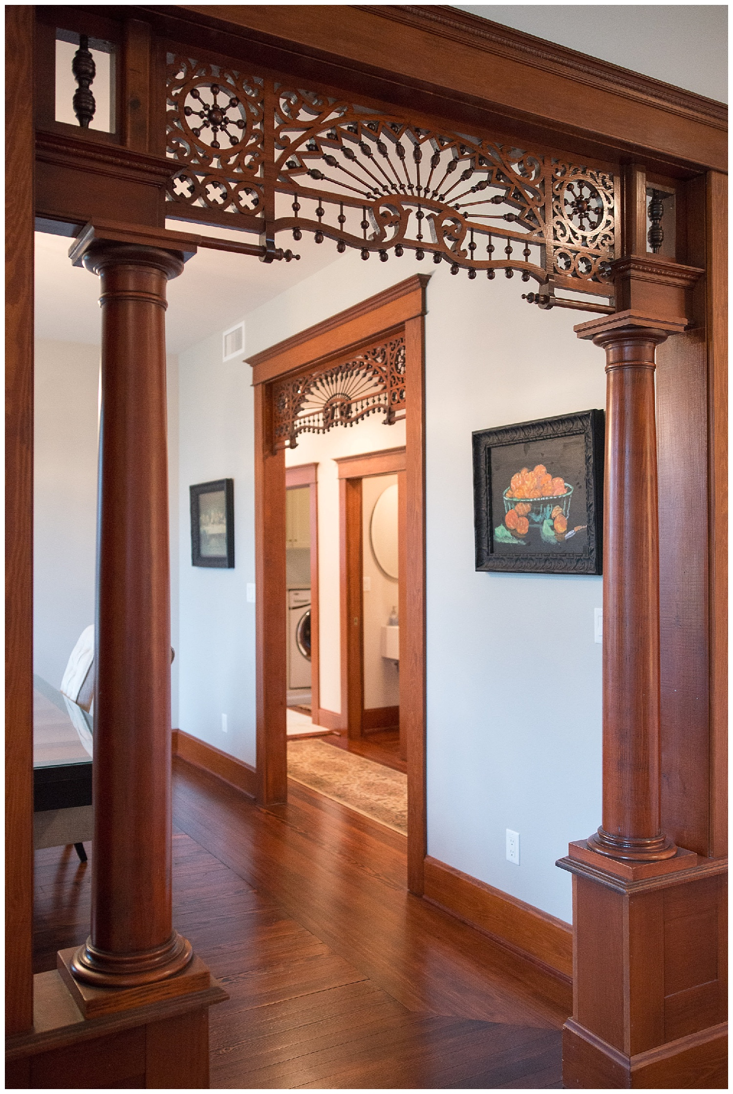 """We're looking into the dining room from the living room/front door. Is this gingerbread trim fabulous or what? Leslie had it removed and cleaned """"to give it another 100 years"""". The painted bowl of oranges on the wall came from the  ARC auction . An Alice Waters print she found in the backroom at Fresh Digs was at the framers."""