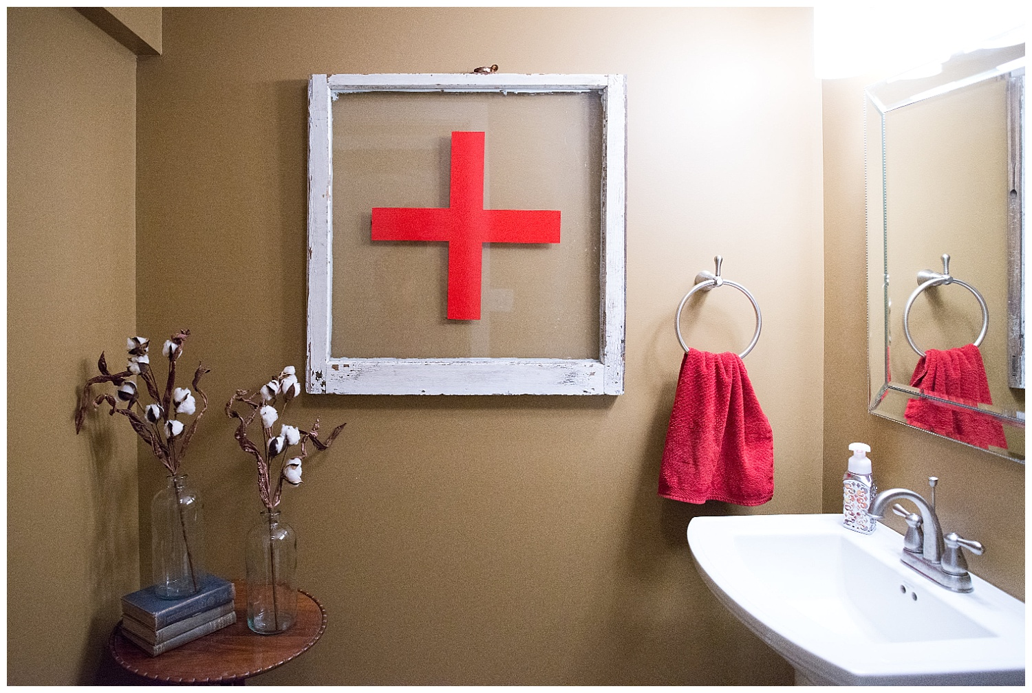 "Great colors going on in this bathroom.  The paint color is ""Cardboard"" by Sherwin Williams.  The red cross window came from Fresh Digs and the old books on the little round table came from an auction."