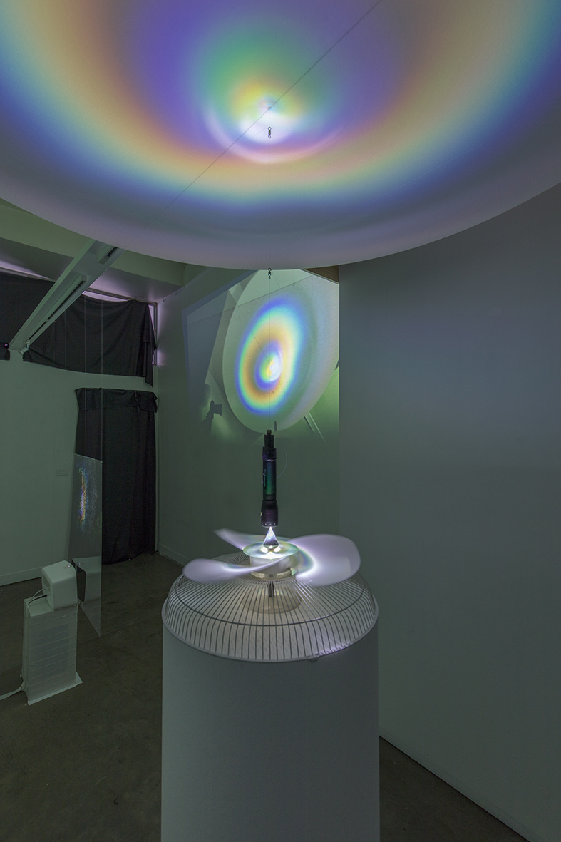 installation view, 2018 - speaker, clear film, video projection (background) kinetic sculpture object foreground