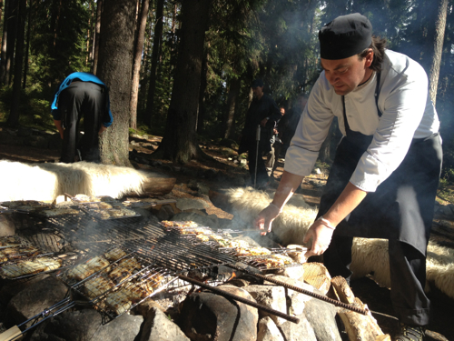 A chef cooks fish and cheese over a campfire.