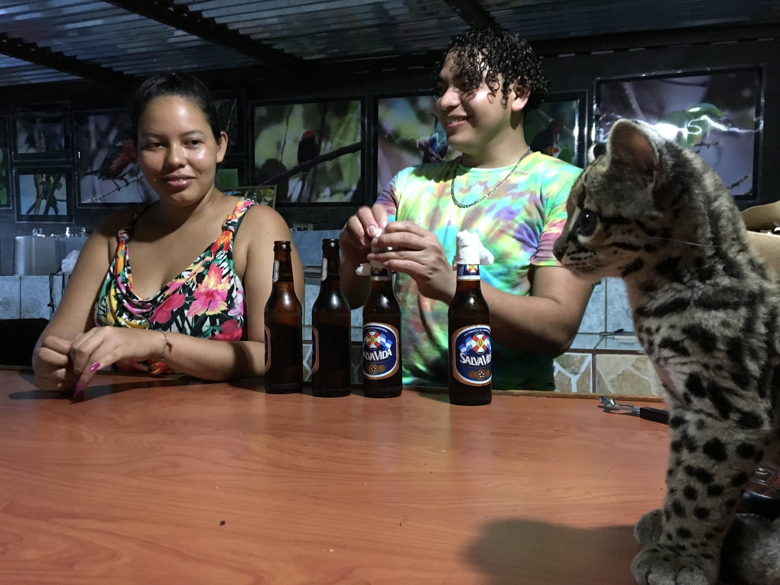 Ocelot and beers. The women who helped tend the young ocelot until its big enough to roam the forest on its own.