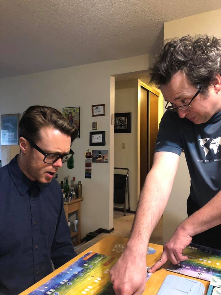 This is not posed. This is totally Non Birding Bill trying to explain the rules of Wingspan to  Jeremy Messersmith .