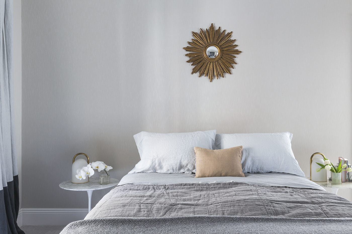The soft and elegant master bedroom is highlighted by antique pieces, dramatic artwork and gold accessories.