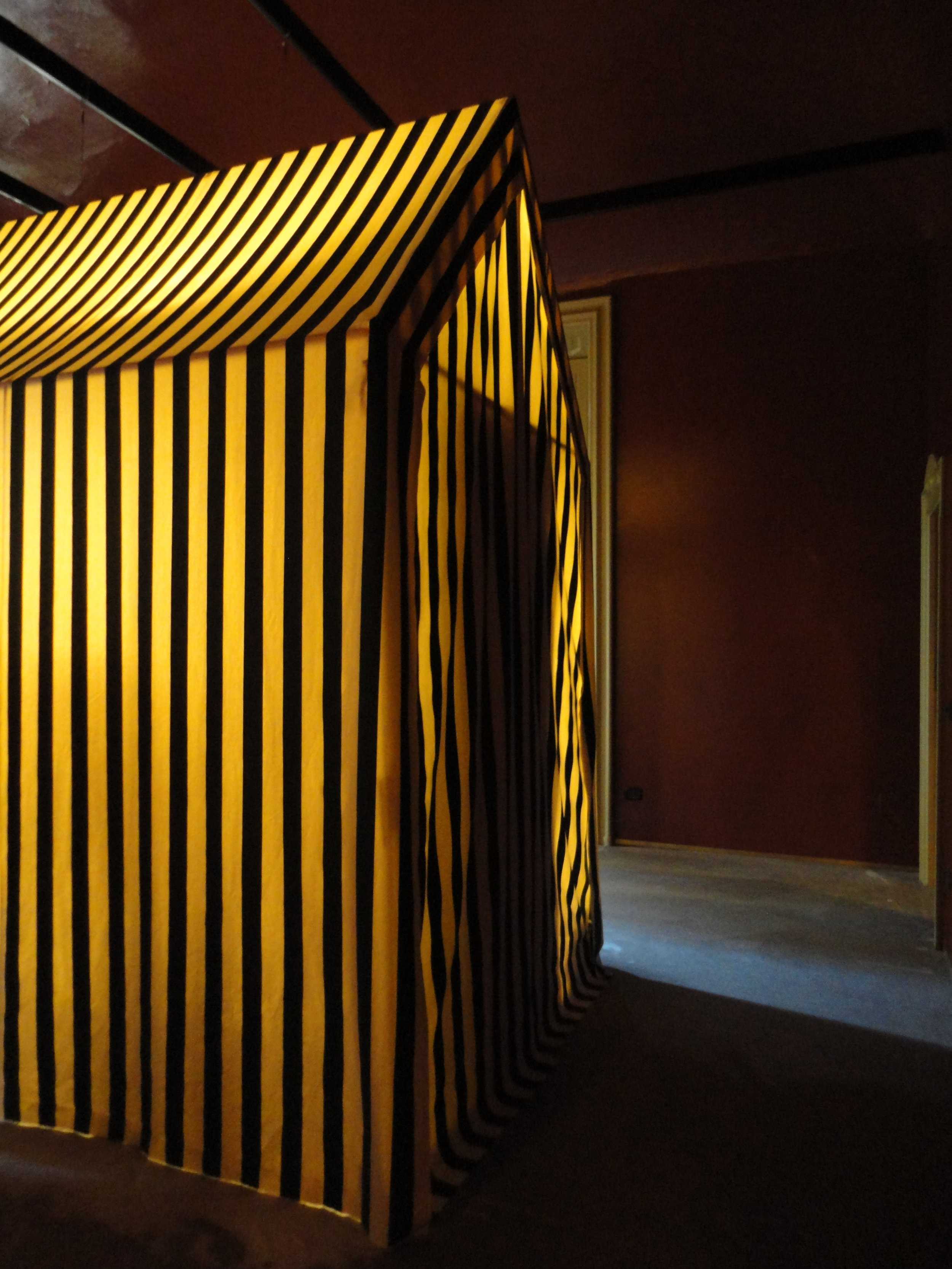 A striped tent illuminated by only candles