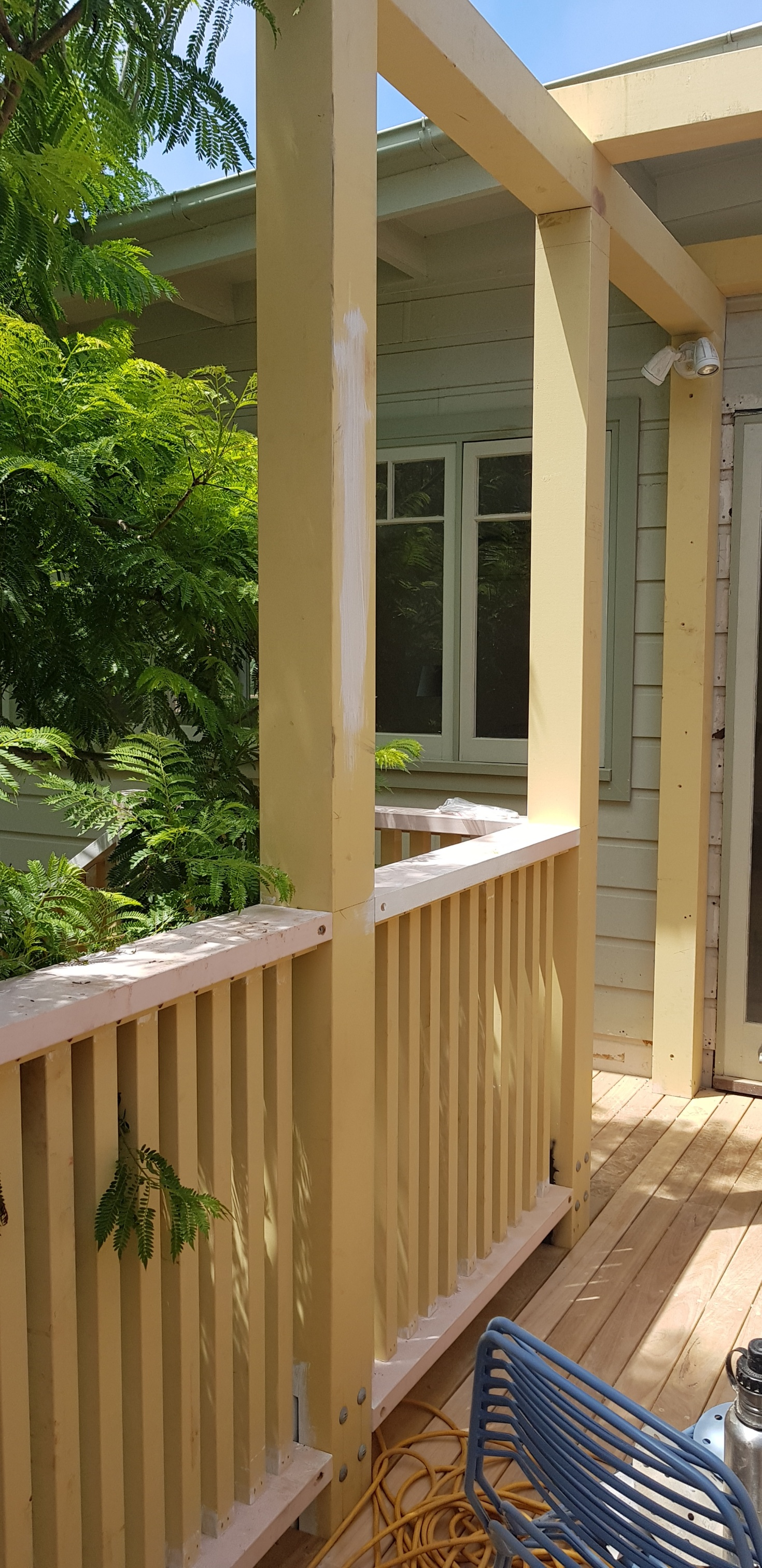 The pergola is to be painted a fresh white to contrast against the green landscaping.
