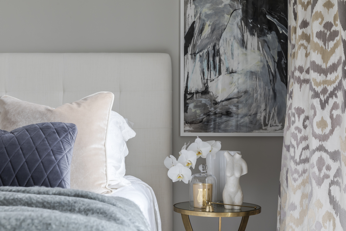 At Jersey Road, the metallic side table and accessories add a warm glow to the master bedroom.
