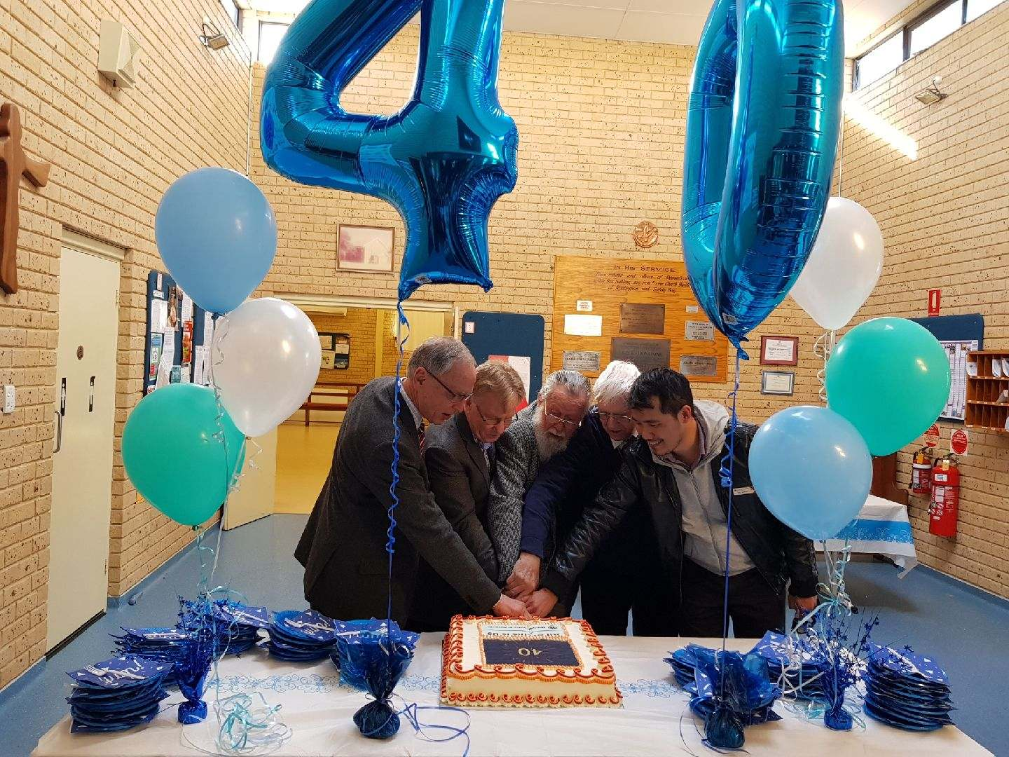 Minister's, past and present, cutting the Anniversary Cake