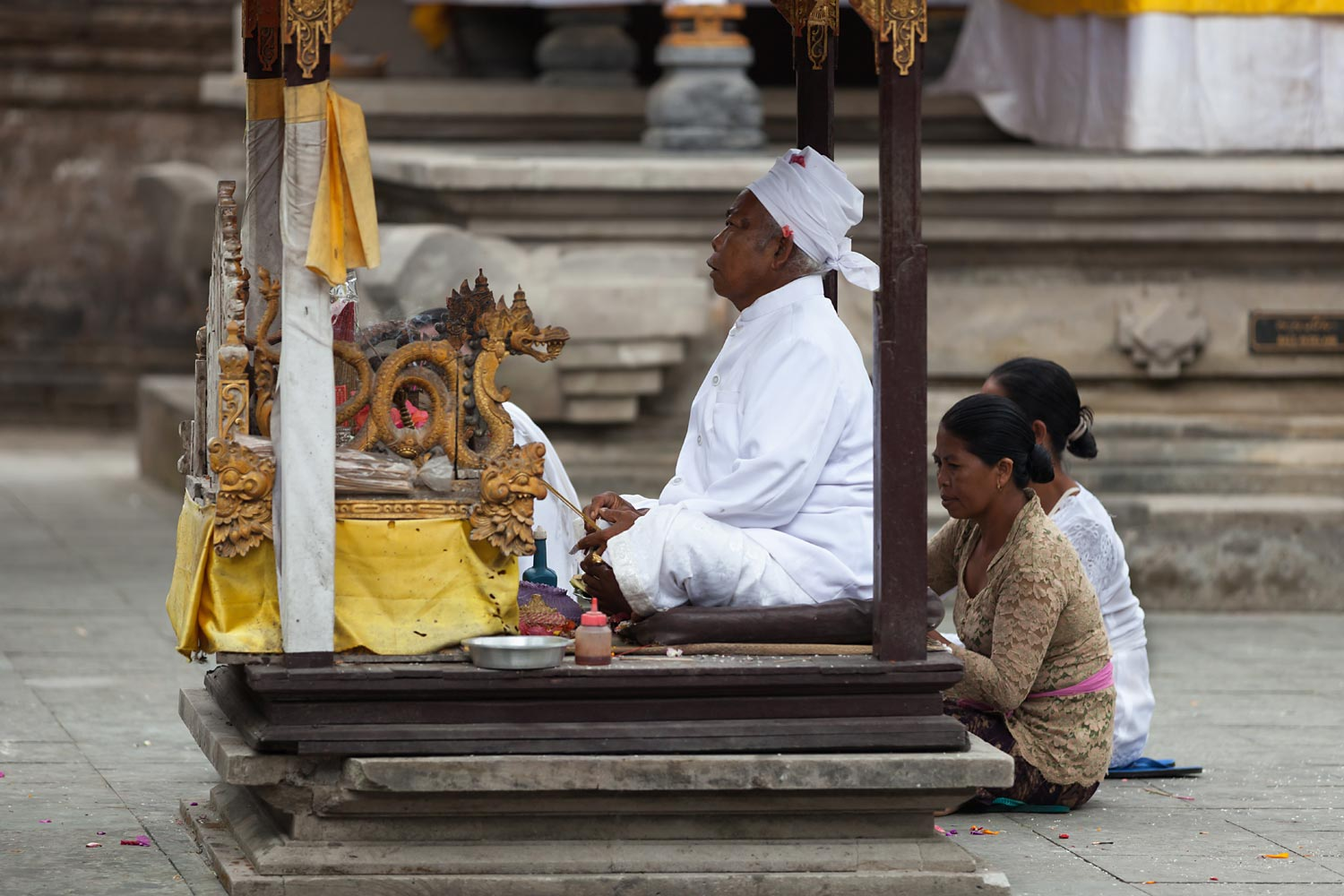 A priest tended by assistants in a temple ceremony | Bali