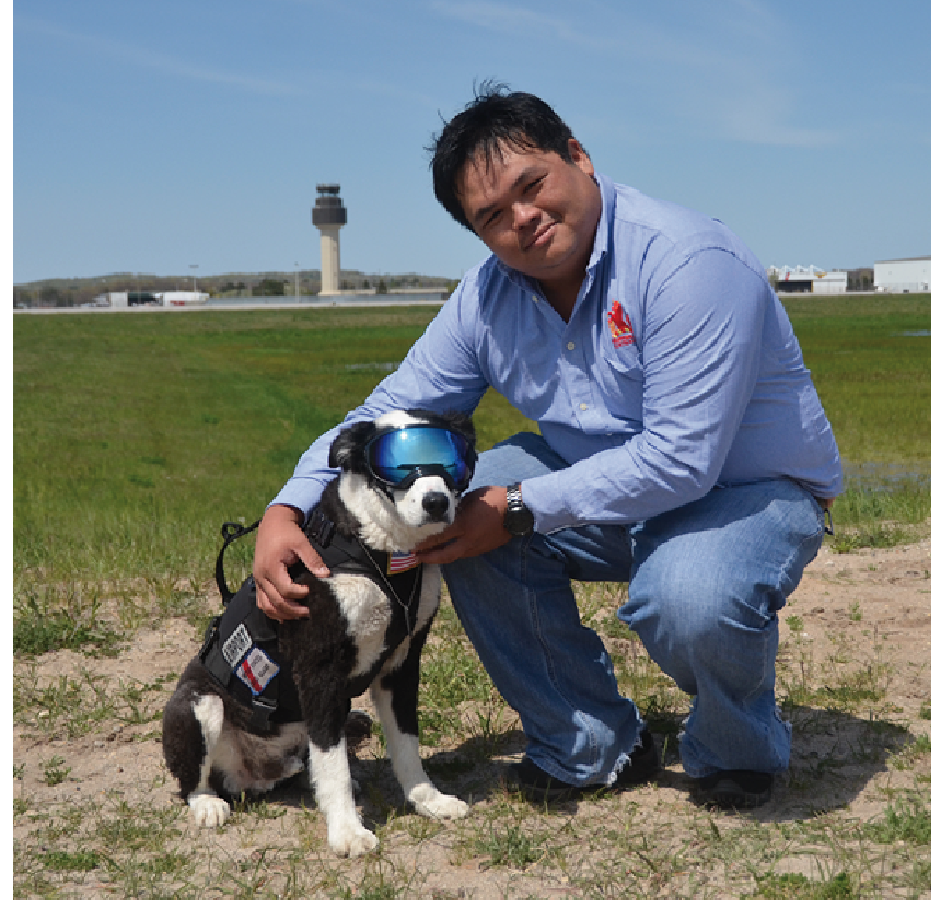 Han with Piper the dog at Cherry Capital Airport. Trained dogs are used to disperse birds at airports and are one of the most effective deterrents for controlling flying feral vermin. (Photo credit: Han Shiong Siah)