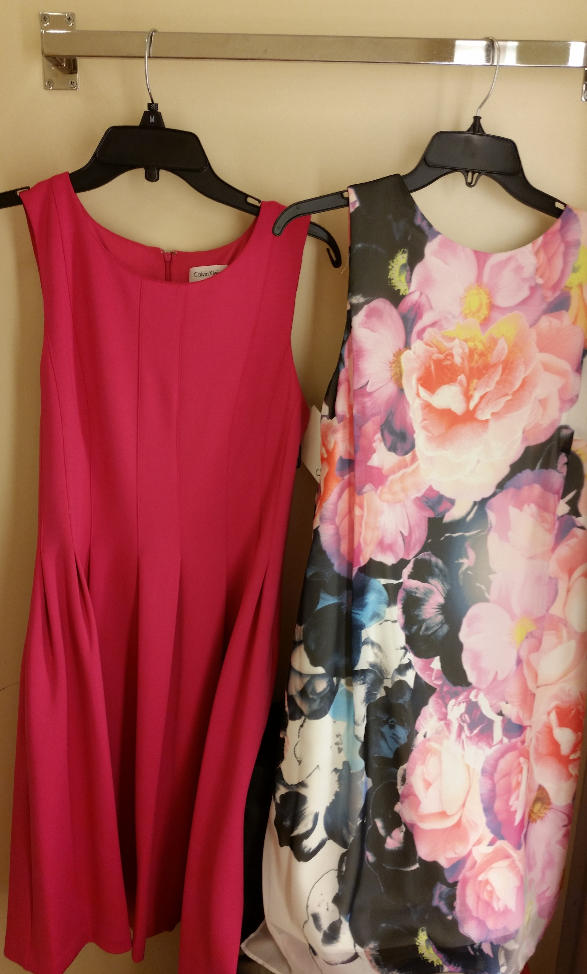 On the left is a Calvin Klein simple pleated sleeveless dress in a beautiful shade of magenta or hot pink. On the right is a sleeveless printed Vince Camuto number. There is a cream colored sheath underneath a beautiful floral printed overlay.
