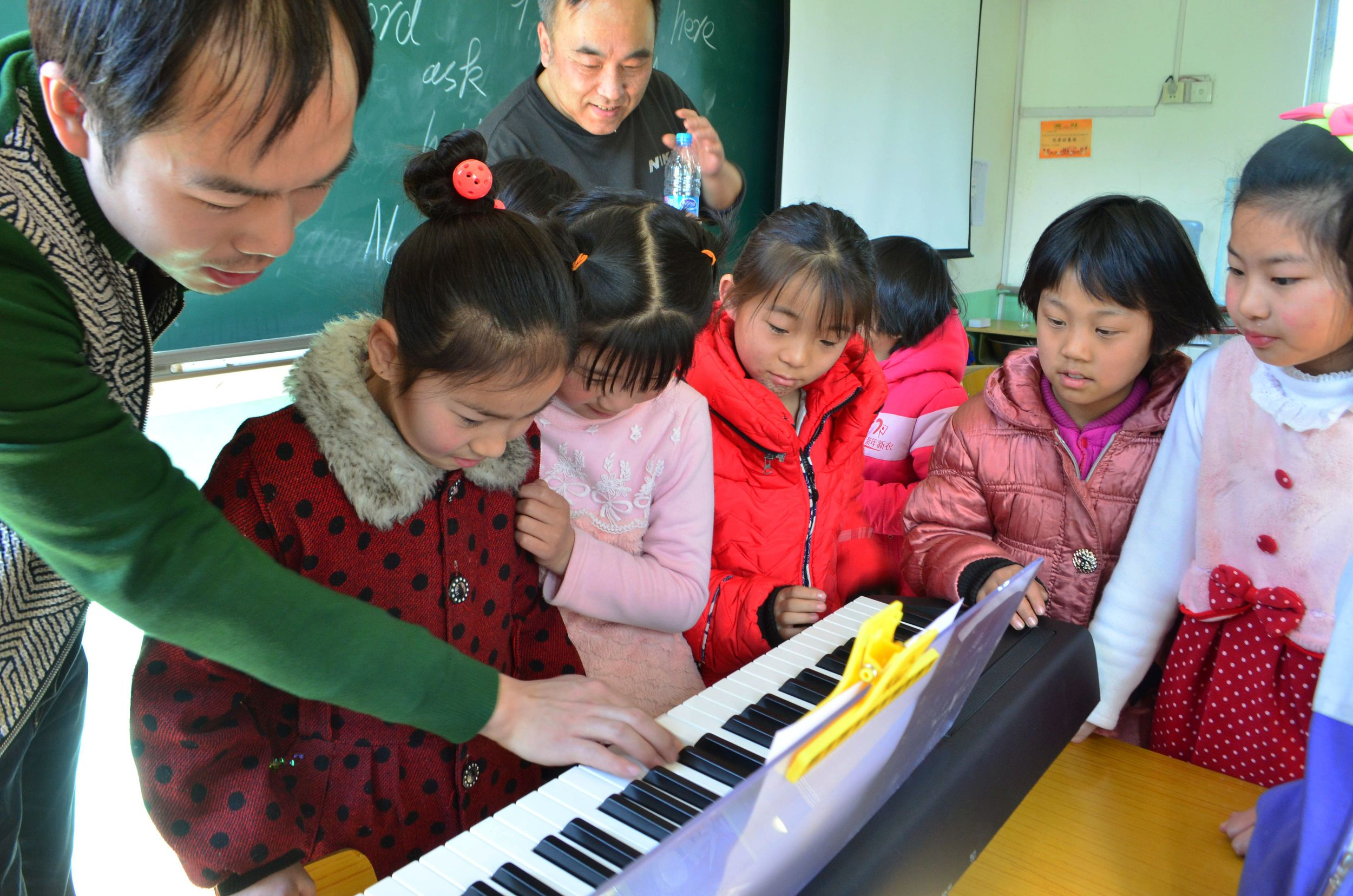 _Teacher and students playing piano老师在教学生弹琴.jpg