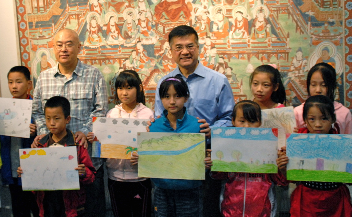 "Author Zheng Yuanjie (left) and US Ambassador Gary Locke pose with migrant children and their ""Peace"" artwork. Some of the art was later given to the US Embassy in Beijing. (Courtesy of US Embassy, Beijing)"