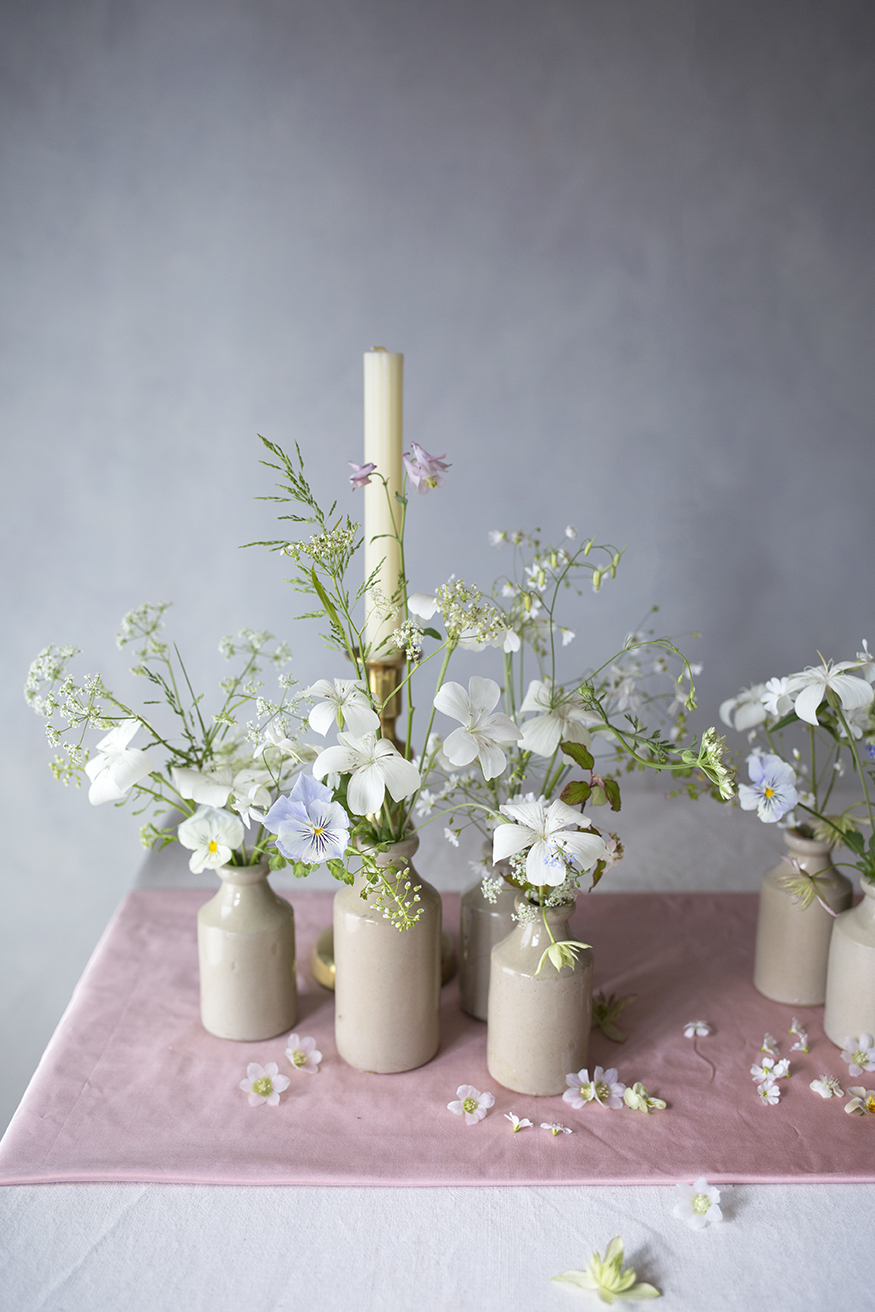 Exploring tablescape design using minimal stoneware vessels of flowers fresh from the garden with scattered allium & clematis blossoms.