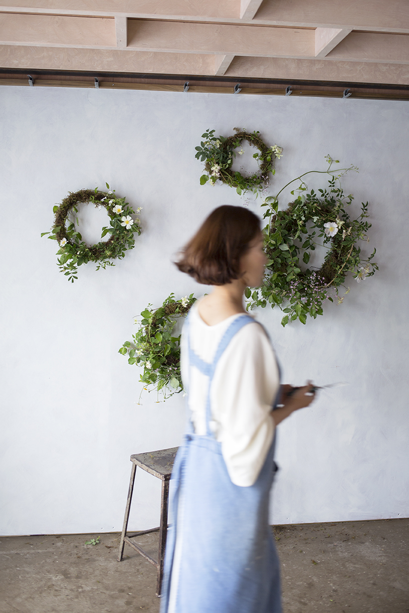 Summer wreath-making: moss bases decorated with dog rose, hedgerow foliage and clematis.