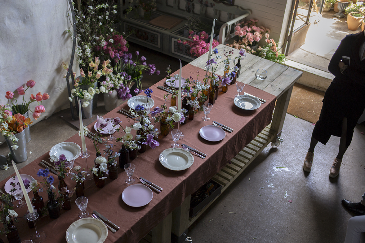 A richly coloured combination of white, lilac, blue and purple flowers arranged in amber glass medicine bottles for a sumptuous spring tablescape.