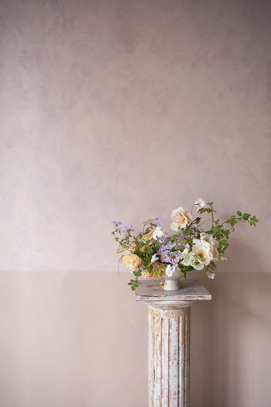 A 'demo' table centrepiece in a ceramic footed bowl. A palette of creamy yellow, lavender and white. Garden roses, geranium pansies, agrostemma, scabiosa and herb Robert.