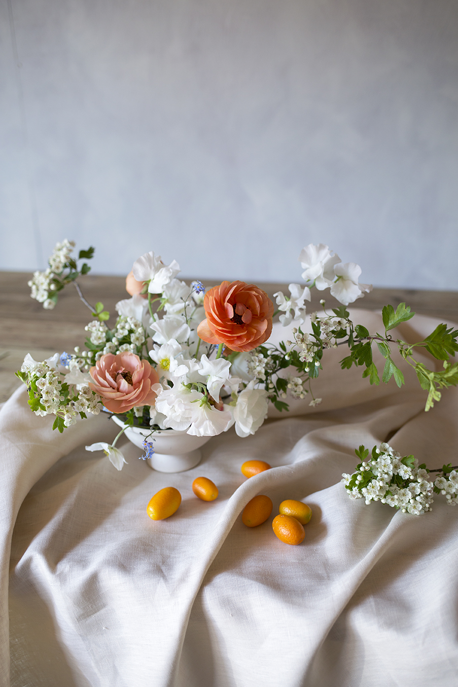 A sweet bowl of hawthorn, sweet peas and apricot ranunculus from our poly tunnel. With indoor-grown kumquats.