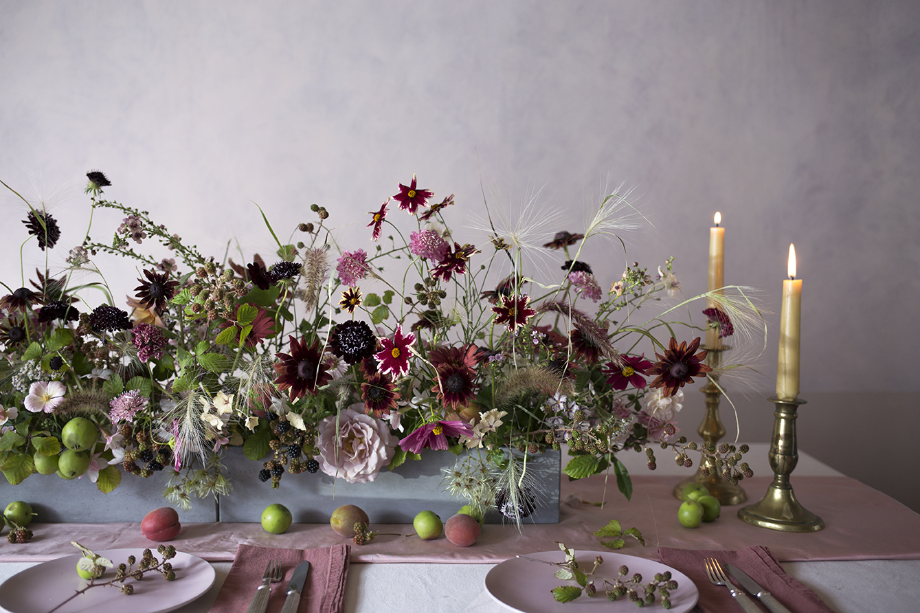 Early autumn tablescape - low, linear vessels of flowers and grasses, blackberry brambles and textural clematis.