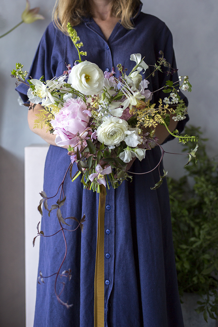 Emma with her bouquet of ranunculus, hawthorn, peonies, bronze clematis and columbine