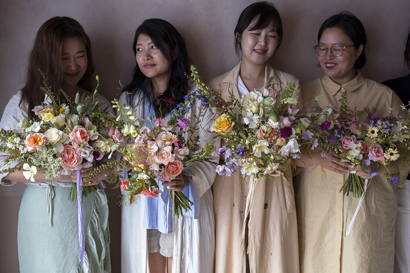 A group holding their bridal bouquets made during a workshop at Aesme Flower Studio