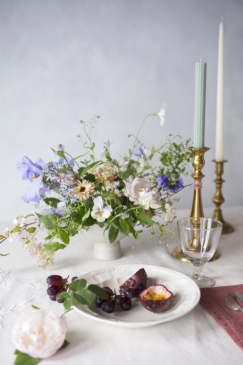 Students' work is styled with linen, candleware and seasonal fruit to create an evocative still-life for use within their portfolio