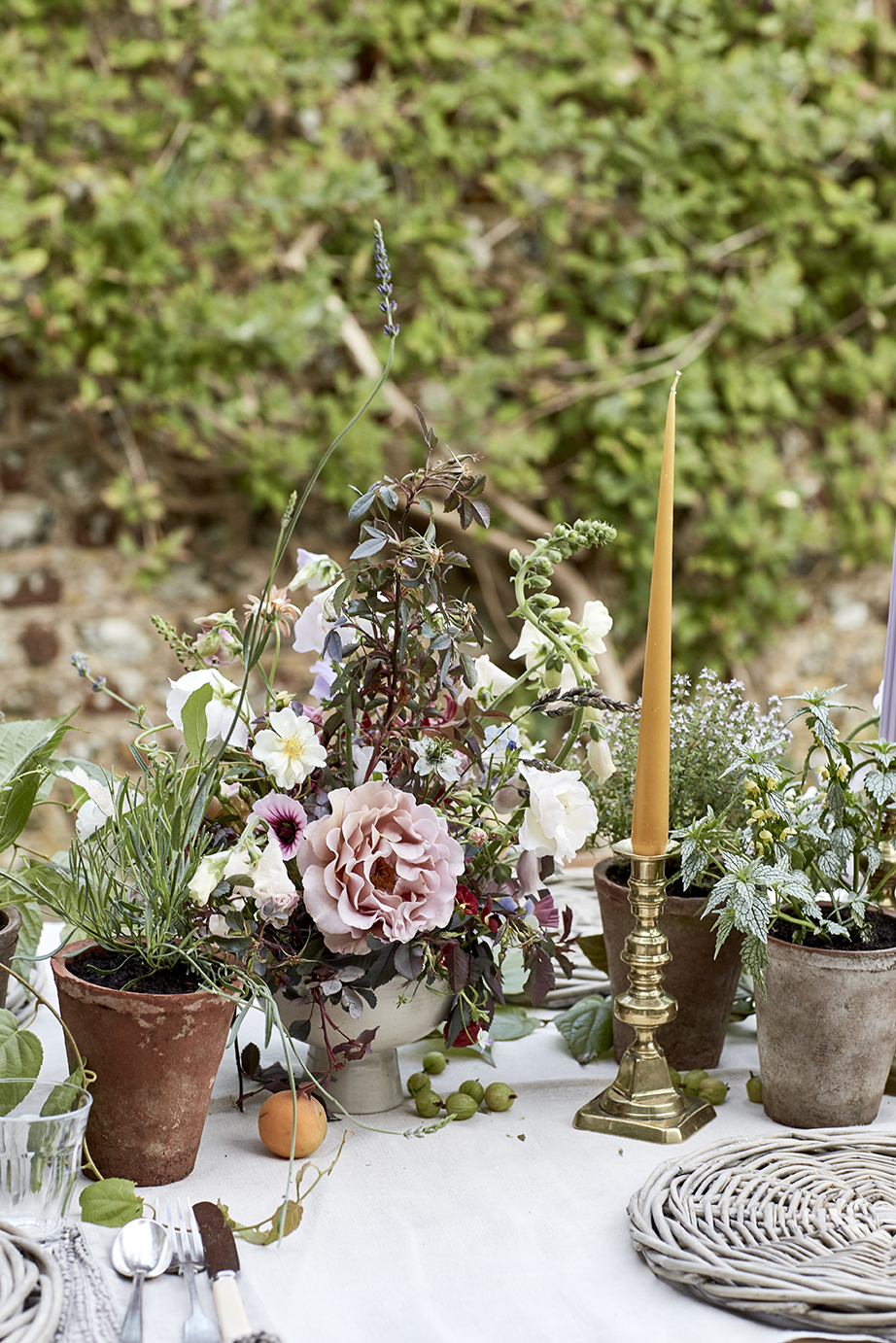 A garden-y tablescape of potted plants, arrangements, candles and fruit   Photographed by  Kristin Perers