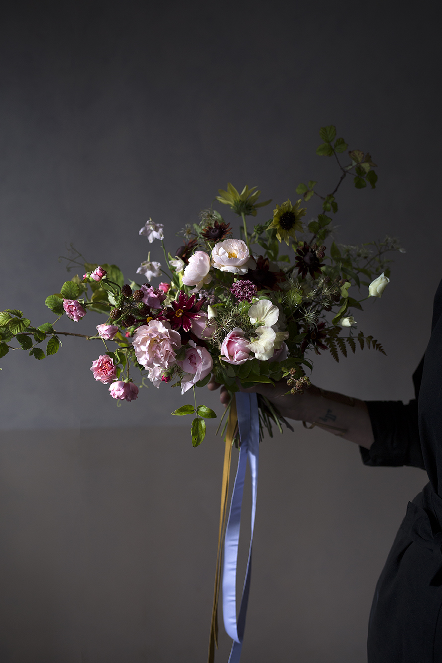 An autumnal bridal bouquet of garden roses, coreopsis, clematis and ferns, tied with lilac and mustard grosgrain ribbons