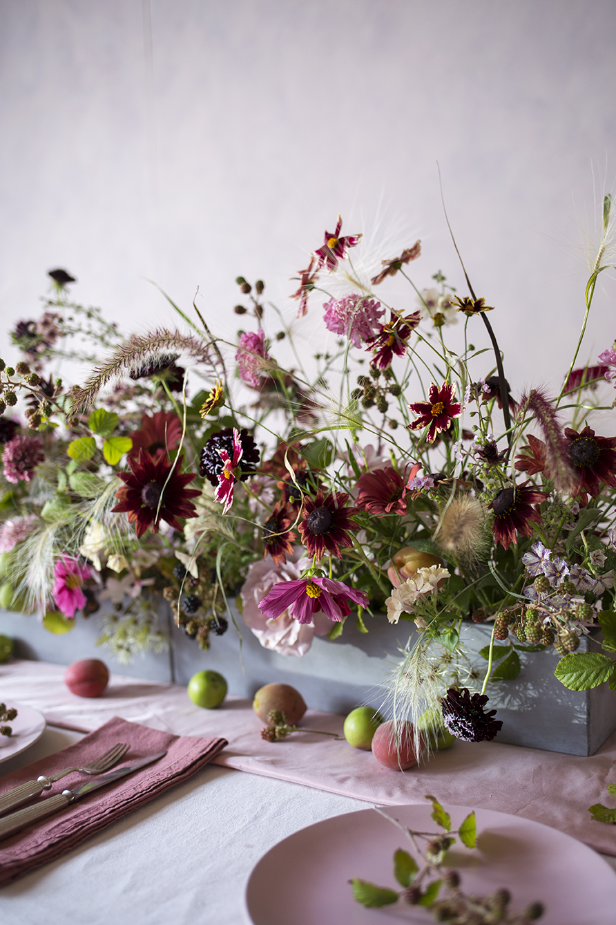 A linear tablescape design of autumn flowers, grasses, herbs and fruit
