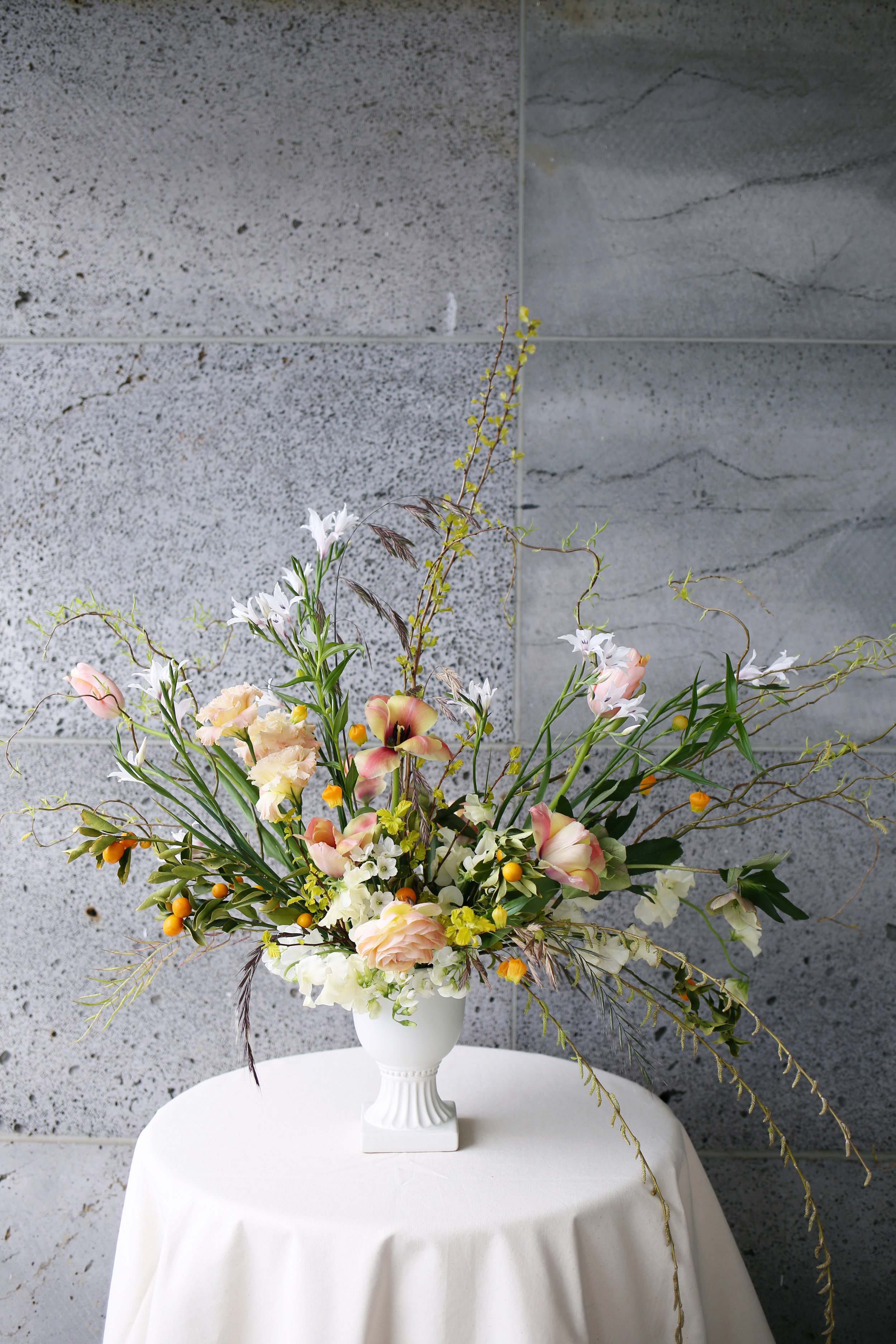 Left: a spring centrepiece of ranunculus, tulips & fritillaria  Above: Urn of willow, ranunculus, tulips and mandarin branches